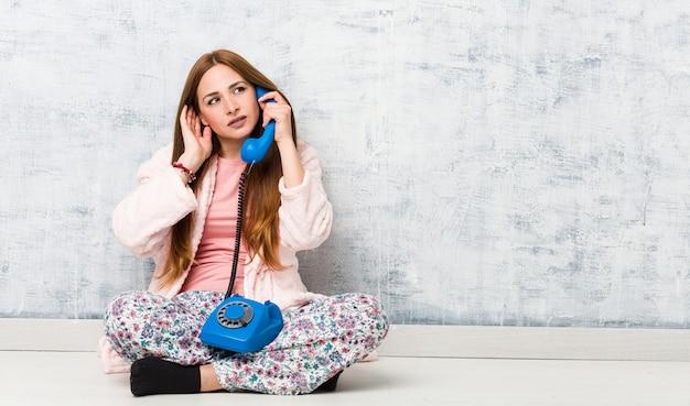 Jovem mulher caucasiana, segurando o telefone fixo, tentando ouvir uma fofoca.