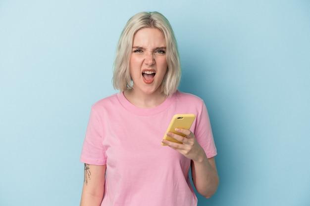 Jovem mulher caucasiana, segurando o telefone móvel isolado no fundo azul, gritando muito zangado e agressivo.