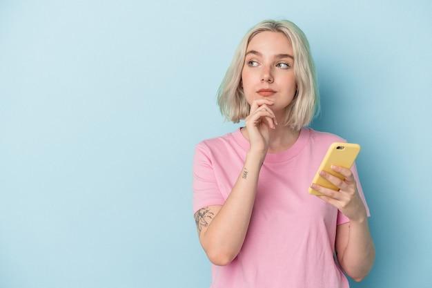 Jovem mulher caucasiana, segurando o telefone móvel isolado sobre um fundo azul, olhando de soslaio com expressão duvidosa e cética.