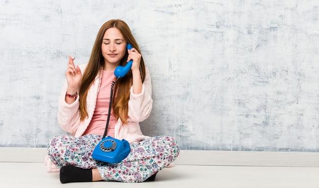 Jovem mulher caucasiana, segurando os dedos do cruzamento de telefone fixo por ter sorte