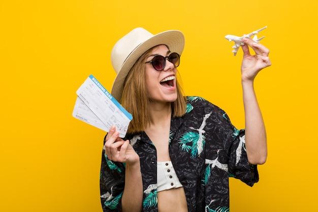 Jovem mulher caucasiana segurando passagens aéreas muito feliz.