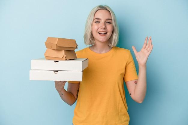 Jovem mulher caucasiana segurando pizzas e hambúrgueres isolados em um fundo azul, recebendo uma agradável surpresa, animada e levantando as mãos.