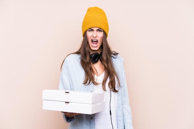 Jovem mulher caucasiana segurando pizzas isoladas, gritando com muita raiva e agressividade.