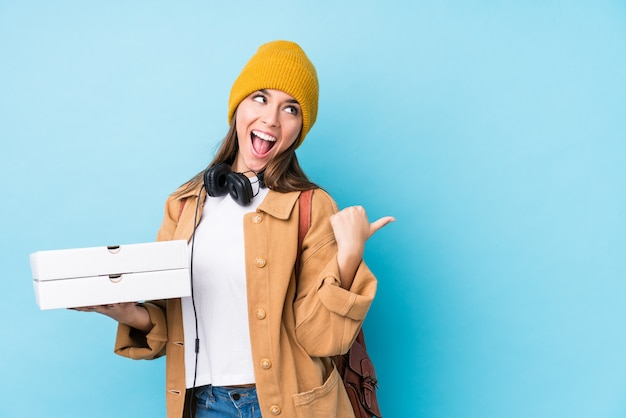 Jovem mulher caucasiana segurando pontos de pizzas com o dedo polegar, rindo e despreocupada.