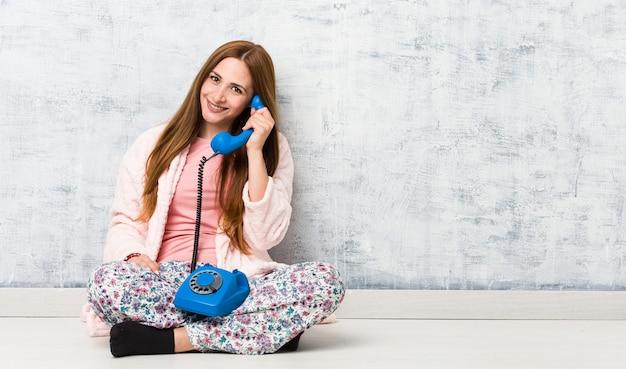 Jovem mulher caucasiana segurando telefone fixo feliz, sorridente e alegre.