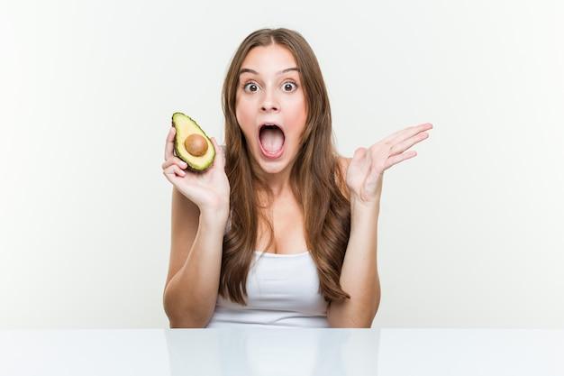 Jovem mulher caucasiana, segurando um abacate comemorando uma vitória ou sucesso