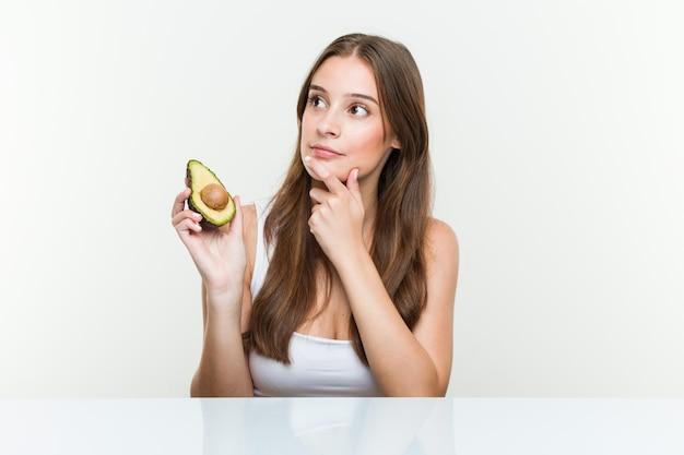Jovem mulher caucasiana, segurando um abacate, olhando de soslaio com expressão duvidosa e cética.