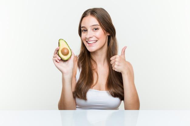 Jovem mulher caucasiana, segurando um abacate sorrindo e levantando o polegar