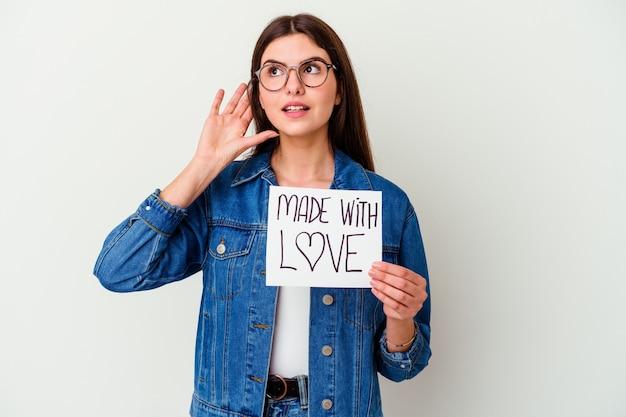 Jovem mulher caucasiana segurando um bilhete com a mensagem: feito com amor