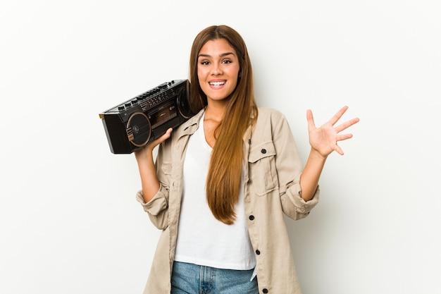 Jovem mulher caucasiana segurando um blaster guetto, recebendo uma agradável surpresa, animada e levantando as mãos.