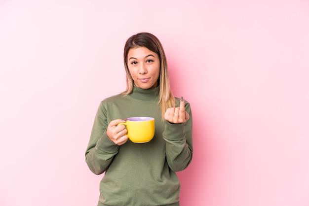 Jovem mulher caucasiana segurando um café apontando com o dedo para você como se fosse um convite para se aproximar.