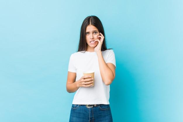 Jovem mulher caucasiana, segurando um café para viagem roendo as unhas, nervosa e muito ansiosa.