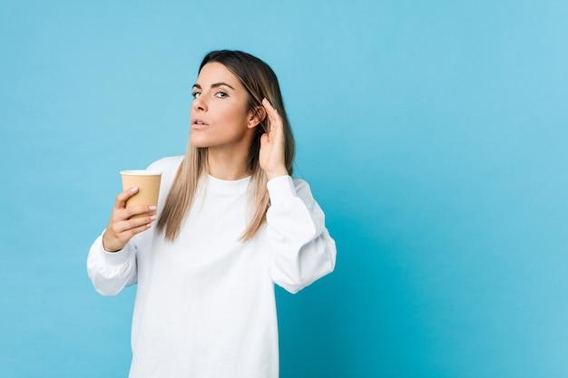 Jovem mulher caucasiana, segurando um café para viagem, tentando ouvir uma fofoca.