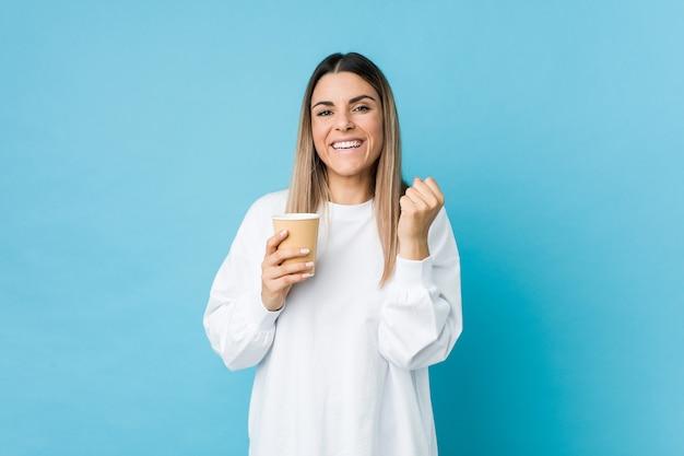 Jovem mulher caucasiana, segurando um café para viagem torcendo despreocupado e animado. conceito de vitória