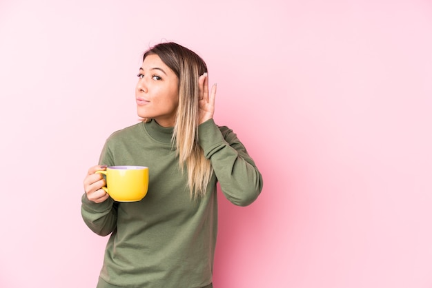 Jovem mulher caucasiana segurando um café, tentando ouvir uma fofoca.