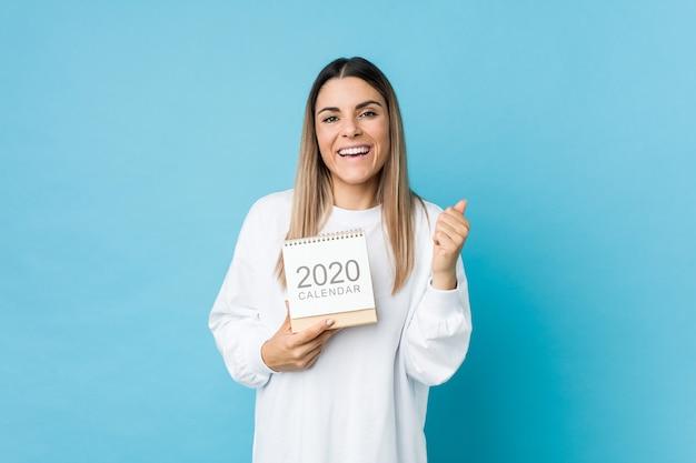 Jovem mulher caucasiana, segurando um calendário 2020 aplaudindo despreocupado e animado. conceito de vitória