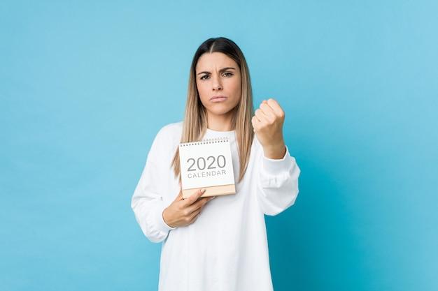 Jovem mulher caucasiana, segurando um calendário 2020, mostrando o punho com expressão facial agressiva.