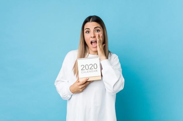 Jovem mulher caucasiana segurando um calendário de 2020 gritando animado para a frente.