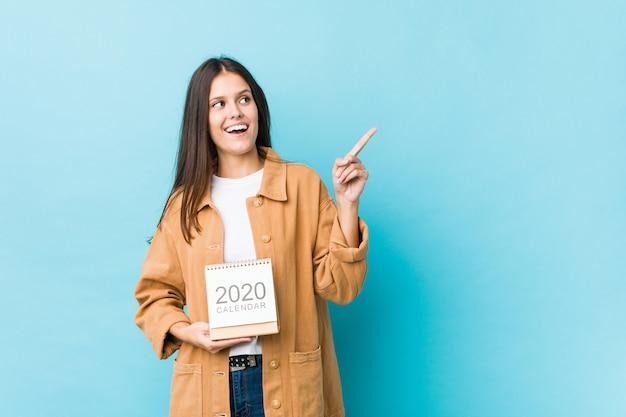 Jovem mulher caucasiana, segurando um calendário de 2020 sorrindo alegremente apontando com o dedo indicador fora.
