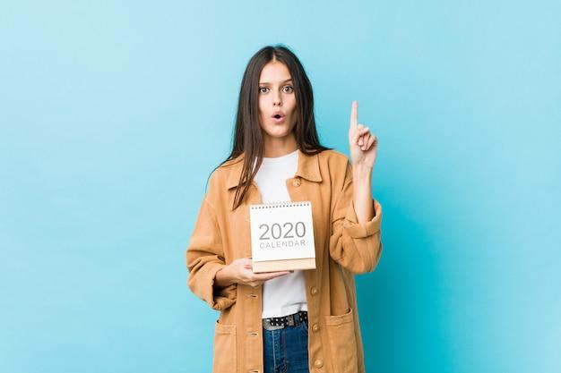 Jovem mulher caucasiana, segurando um calendário de 2020, tendo uma ótima idéia, conceito de criatividade.