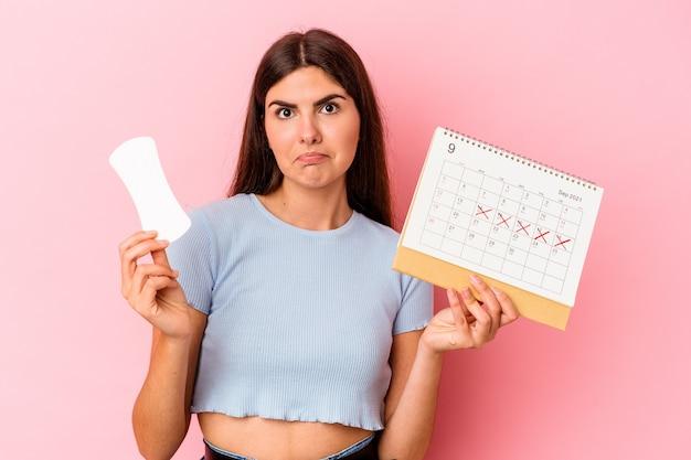 Jovem mulher caucasiana segurando um calendário e uma compressa isolada em um fundo rosa