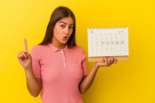 Jovem mulher caucasiana, segurando um calendário isolado em fundo amarelo, tendo uma ótima ideia, o conceito de criatividade.