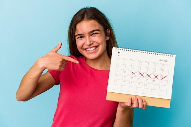 Jovem mulher caucasiana segurando um calendário isolado em um fundo azul