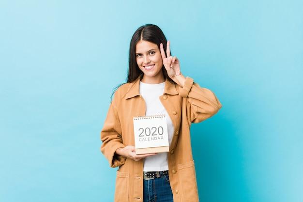 Jovem mulher caucasiana, segurando um calendário mostrando sinal de vitória e sorrindo amplamente.