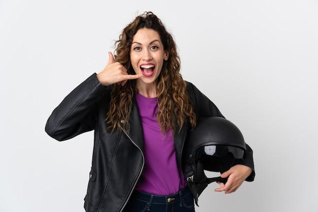 Jovem mulher caucasiana segurando um capacete de motocicleta, fazendo gesto de telefone. ligue-me de volta sinal