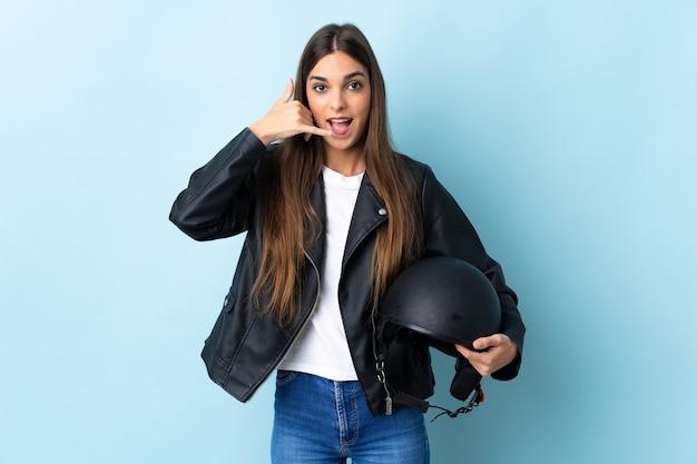 Jovem mulher caucasiana segurando um capacete de motocicleta isolado na parede azul, fazendo gesto de telefone. ligue-me de volta sinal