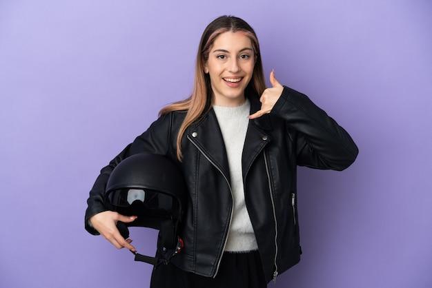 Jovem mulher caucasiana segurando um capacete de motocicleta isolado no fundo roxo, fazendo gesto de telefone. ligue-me de volta sinal