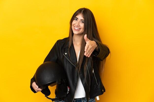 Jovem mulher caucasiana segurando um capacete de motociclista isolado em um fundo amarelo, apertando as mãos para fechar um bom negócio