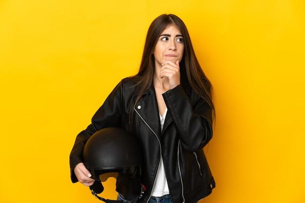 Jovem mulher caucasiana segurando um capacete de motociclista isolado em um fundo amarelo, tendo dúvidas e pensando