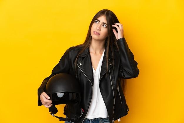 Jovem mulher caucasiana segurando um capacete de motociclista isolado em um fundo amarelo, tendo dúvidas
