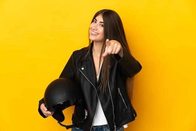 Jovem mulher caucasiana segurando um capacete de motociclista isolado na parede amarela apontando para a frente com uma expressão feliz