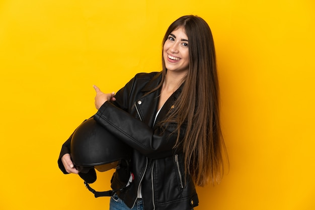 Jovem mulher caucasiana segurando um capacete de motociclista isolado na parede amarela apontando para trás