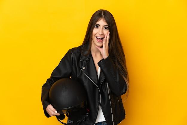 Jovem mulher caucasiana segurando um capacete de motociclista isolado na parede amarela com expressão facial surpresa e chocada