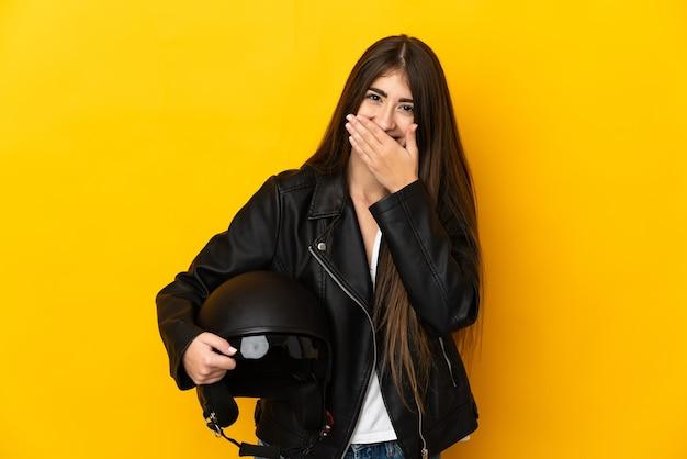 Jovem mulher caucasiana segurando um capacete de motociclista isolado na parede amarela, feliz e sorridente, cobrindo a boca com a mão