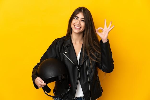 Jovem mulher caucasiana segurando um capacete de motociclista isolado na parede amarela, mostrando um sinal de ok com os dedos