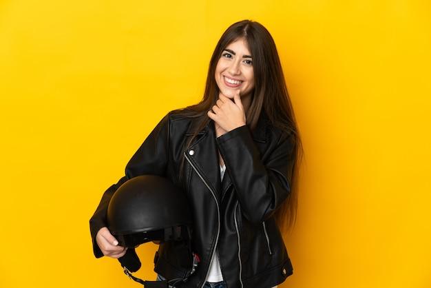 Jovem mulher caucasiana segurando um capacete de motociclista isolado na parede amarela, olhando para o lado e sorrindo