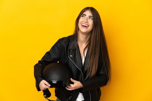 Jovem mulher caucasiana segurando um capacete de motociclista isolado na parede amarela rindo