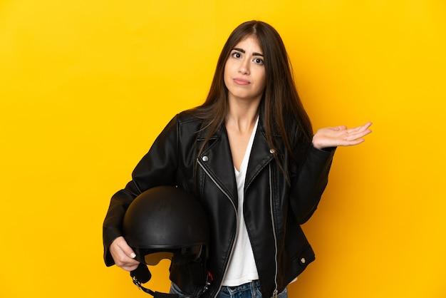 Jovem mulher caucasiana segurando um capacete de motociclista isolado na parede amarela, tendo dúvidas ao levantar as mãos