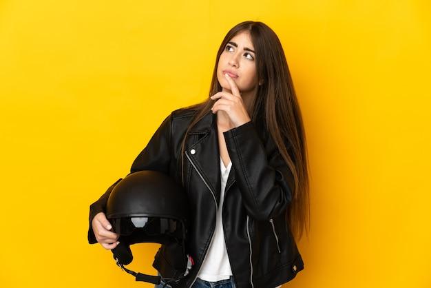 Jovem mulher caucasiana segurando um capacete de motociclista isolado na parede amarela, tendo dúvidas enquanto olha para cima