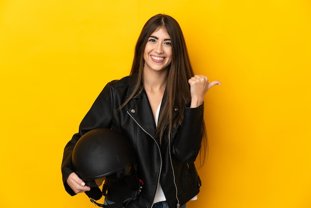 Jovem mulher caucasiana segurando um capacete de motociclista isolado
