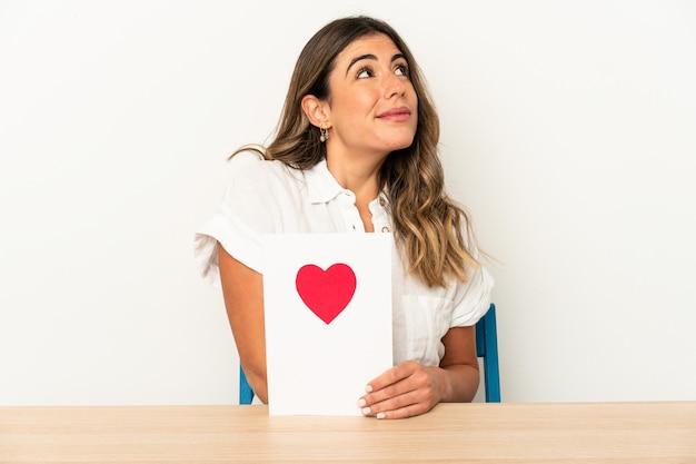 Jovem mulher caucasiana segurando um cartão de dia dos namorados isolada, sonhando em alcançar objetivos e propósitos