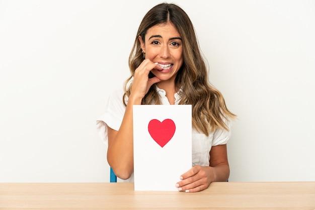 Jovem mulher caucasiana segurando um cartão de dia dos namorados isolada unhas roendo, nervosa e muito ansiosa.