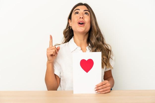 Jovem mulher caucasiana, segurando um cartão de dia dos namorados isolado apontando para cima com a boca aberta.