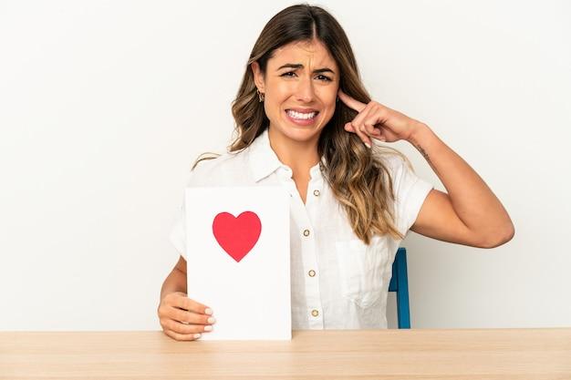 Jovem mulher caucasiana, segurando um cartão de dia dos namorados isolado, cobrindo as orelhas com as mãos.