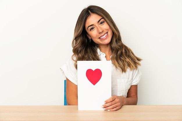 Jovem mulher caucasiana, segurando um cartão de dia dos namorados isolado, feliz, sorridente e alegre.