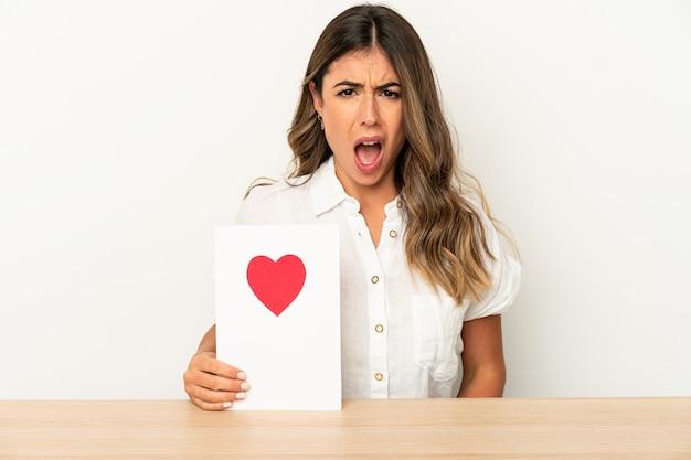 Jovem mulher caucasiana segurando um cartão de dia dos namorados isolado gritando muito zangado e agressivo.